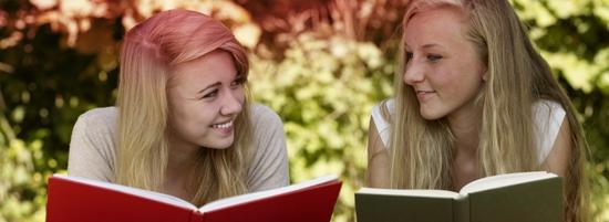 Imagine cu două tinere care citesc o carte. Fotografia ilustrează numeroasele mituri asociate menstruaţiei.