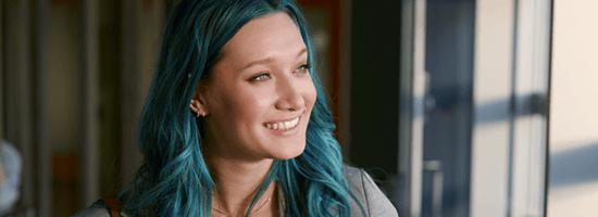 O fată cu părul albastru care zâmbește.