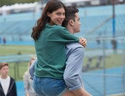 Fotografia ilustrează un cuplu de tineri care se află pe stadion.
