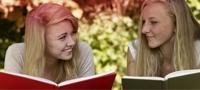 Imagine cu două femei care citesc o carte. Fotografia ilustrează numeroasele mituri care planează în jurul menstruaţiei.